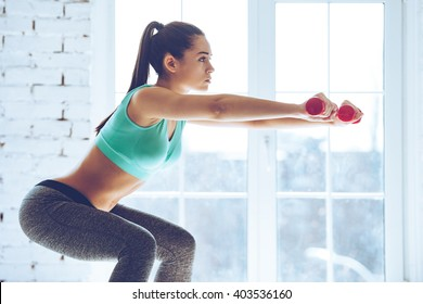 Feel the burn in buttocks. Side view of beautiful young woman in sportswear doing squat and holding dumbbells while standing in front of window at gym