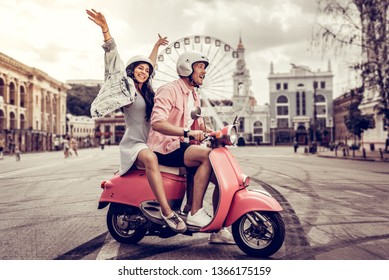 I feel free. Delighted nice woman holding her hands up while sitting behind her boyfriend on the motorcycle
