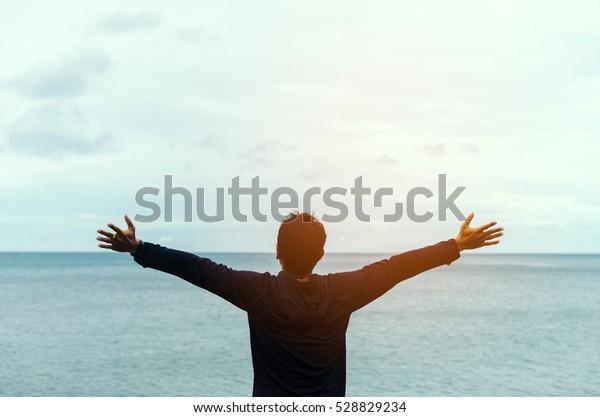 Sentirsi bene e concetto di libertà. Copia spazio di uomo felice alzare le mani su sfondo spiaggia. Stile vintage del filtro del colore.