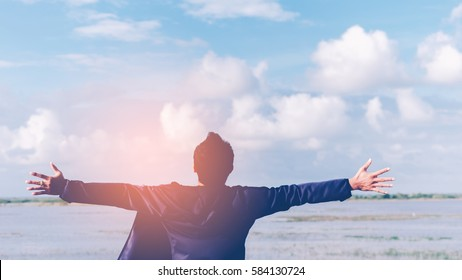 Feel good freedom and travel adventure concept. Copy space of happy man raise hands on river and blue sky white cloud background. Vintage tone filter effect color style.