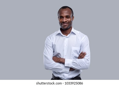 I feel happy. Handsome cheerful dark-eyed afro-american man smiling and standing and having his arms crossed