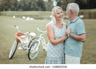 Feel your heartbeats. Beautiful retirement embracing her husband while enjoying her family life