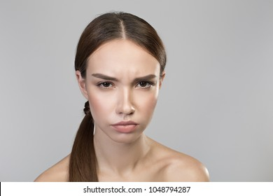 Feeling anger. Portrait of young disappointed naked woman is looking at camera with annoyance. Isolated background