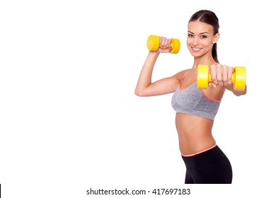 Feeling awesome! Looking even better! Shot of a beautiful and sporty young woman lifting up weights against white background.