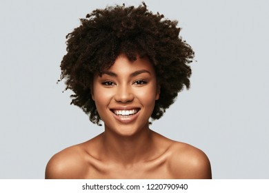 Feeling beautiful. Attractive young African woman looking at camera and smiling while standing against grey background