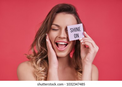 Feeling beautiful.  Attractive young woman covering face with a small poster and smiling while standing against pink background