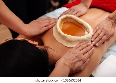 Feeling benefits. Woman having kati vasti Ayurveda treatment in salon while warm oil placing on her lower back