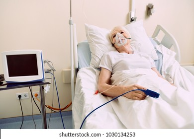 Feeling better today. Elderly woman undergoing treatment and staying in a hospital with a pulse oximeter and a respiratory support.