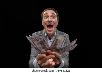 Feeling bid passion about money. Portrait of young crazy entrepreneur is standing and demonstrating dollars while looking at camera with wide-eyed and open mouth. Isolated background