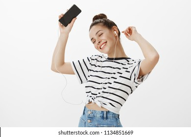 Feeling boost of happiness from hearing great songs in earbuds. Pleased feminine girl in striped t-shirt, dancing with raised hands, holding smartphone, smiling broadly, listening music in earphones