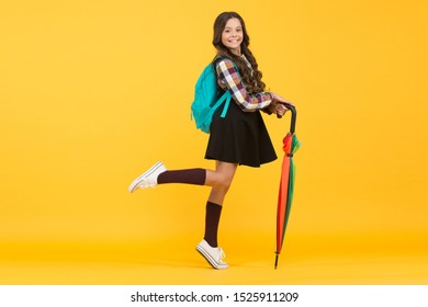 Feeling carefree. Fall weather forecast. Rainy september. Adorable small schoolgirl with backpack. Schoolgirl daily life. Girl with umbrella. Happy childhood. Kid happy schoolgirl with umbrella.