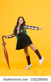 Feeling carefree. Happy childhood. Kid happy schoolgirl with umbrella. Fall weather forecast. Rainy september. Adorable small schoolgirl with backpack. Schoolgirl daily life. Girl with umbrella.