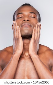 Feeling clean and fresh. Young shirtless African man touching his face with hands and keeping eyes closed while standing against grey background