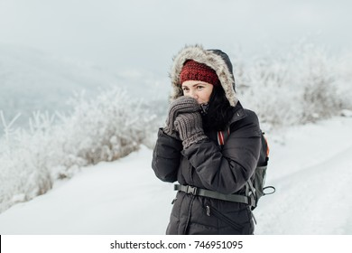 Feeling cold - a woman dressed warm blowing on her hands. Portrait of a cheerful female tourist trying to keep warm in a snowy country.