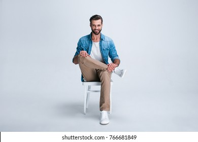 Feeling comfortable anywhere. Full length of handsome young man looking at camera with smile while sitting against white background