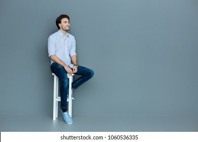 Feeling comfortable. Joyful positive young man sitting on a stool and smiling while being in a great mood