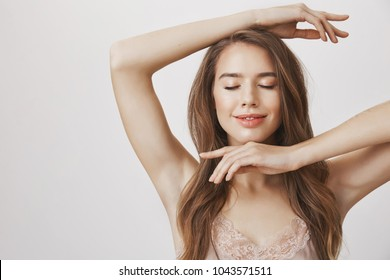 Feeling confident and carefree. Good-looking european female showing her sensuality and feminine features, framing face with clear skin with hands, smiling playfully and dreaming with closed eyes