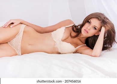 22f51cab7d Feeling confident in her perfect body. Attractive young brown hair woman in lingerie  lying in