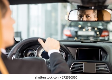 Feeling confident in his new car. Rear view of confident senior man in formalwear sitting on drivers place in car and looking at mirror