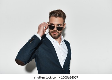 Feeling confident in his style. Handsome young man in formalwear adjusting his eyewear and looking away while standing against grey background