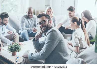 Feeling confident in his team. Group of cheerful young business people sitting at the office desk together and discussing something while young man looking over shoulder and smiling