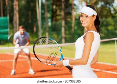 Feeling confident of winning. Beautiful young woman holding tennis racket and looking over shoulder with smile while man in sports clothing standing in the background