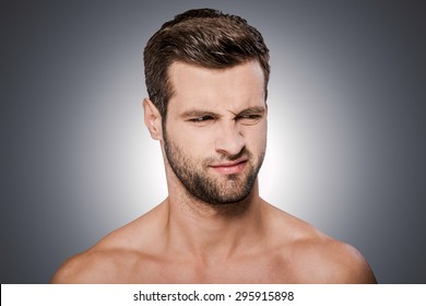 Feeling disgust. Portrait of frustrated young shirtless man looking away and grimacing while standing against grey background
