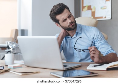 Feeling exhausted. Frustrated young handsome man looking exhausted while sitting at his working place and carrying his glasses in hand