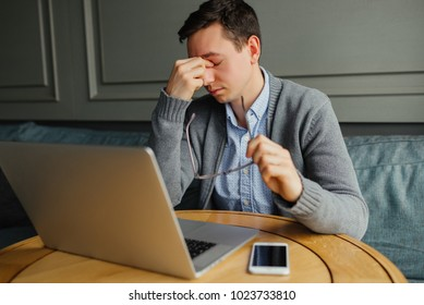 Feeling exhausted. Frustrated young man massaging his nose and keeping eyes closed while working in cafe.