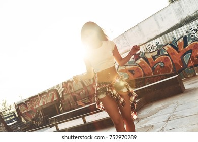 Feeling free to be herself. Attractive young woman walking through the skate park while spending time outdoors