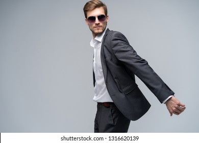 Feeling free and comfortable in his style. Handsome young man in full suit and sunglasses moving in front of gray background