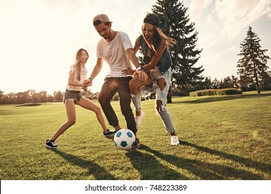 Feeling free with friends. Full length of young smiling people in casual wear running while playing soccer outdoors