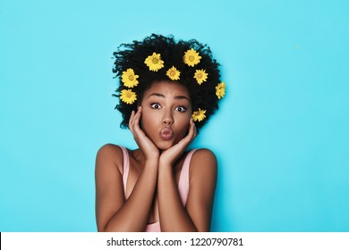 Feeling free to go crazy. Top view of attractive young African woman looking at camera and puckering while lying against blue background