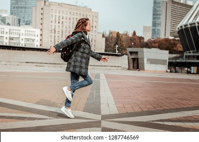 Feeling free. A happy girl skipping through the city center