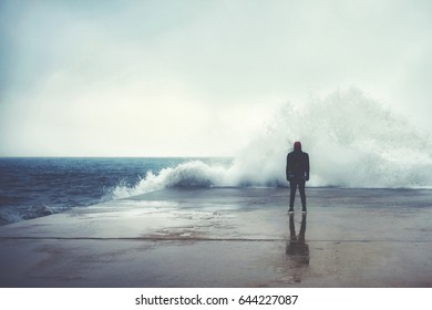 Feeling of freedom, back view of adult man standing on pier facing to the sea with big waves beats against the shore on a cloudy autumn day, alone depress person,the power of nature, storm on seashore