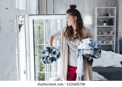 Feeling furious. Ex wife standing near the window feeling furious while throwing square shirt of ex husband away