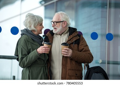 Feeling glad. Profile of cheerful gray-haired man and woman are standing together at international airport with luggage and hugging. They are looking at each other with smile and drinking espresso