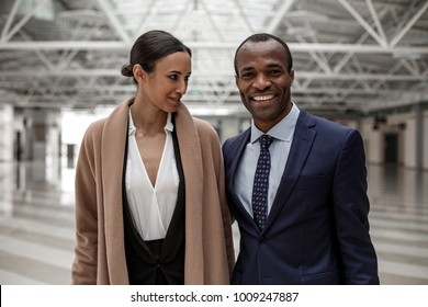 Feeling gladness. Portrait of cheerful stylish african businessman in suit is looking at camera with wide smile while hugging attractive lady at big hall