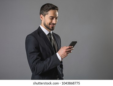 Feeling happiness. Waist up portrait of cheerful businessman in suit surfing in internet. Isolated on grey background. Copy space in left side
