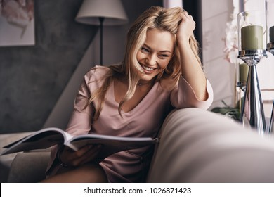 Feeling so happy! Attractive young woman in elegant dress keeping hand in hair and smiling while sitting on the sofa