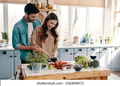 Feeling happy. Beautiful young couple cooking dinner while standing in the kitchen at home