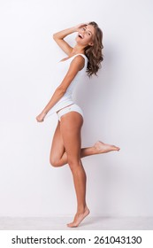 Feeling so happy. Full length of attractive young brown hair woman in tank top and panties posing against white background