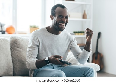 Feeling happy. Handsome young African man holding a remote control and laughing while sitting on the sofa at home