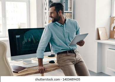 Feeling happy. Young modern businessman looking away and smiling while working in the office
