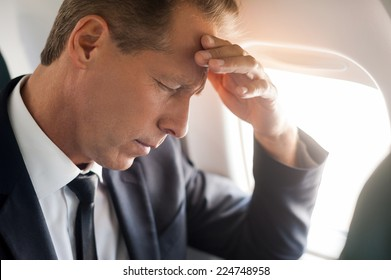 Feeling headache. Frustrated mature businessman touching his forehead with hand and keeping eyes closed while sitting at his seat in airplane