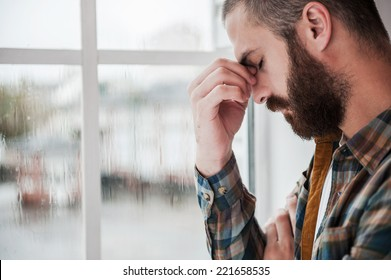 Feeling hopeless. Depressed young bearded man keeping eyes closed and touching his face while standing near the window