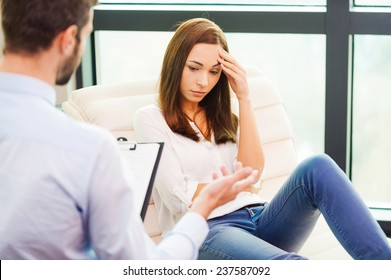 Feeling so hopeless. Depressed young woman sitting at the chair and holding hand on head while male psychiatrist sitting in front of her and holding clipboard