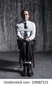 Feeling hopeless. Shocked businessman sitting at the chair and shouting while being tied up