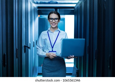 Feeling inspired. Alert young professional woman smiling and holding her laptop