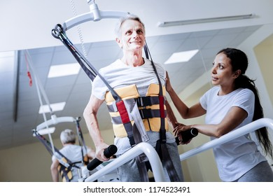 Feeling inspired. Positive smiling aged patient wearing a necessary body vest while going through the process of rehabilitation after a terrible injury with a kind attentive reliable medical worker